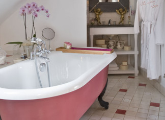 Une salle de bains ouverte sur la chambre avec une baignoire en fonte rose