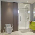 Une douche et un lave-linge cachés derrière des portes coulissantes. Gros plan sur la douche