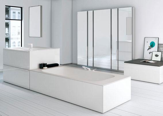 Un îlot dans la salle de bains, avec une baignoire, prolongée par le point d'eau