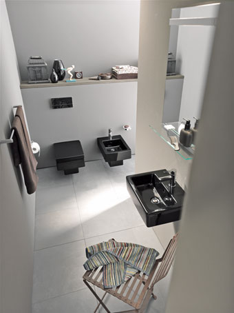 Une salle de bains avec un lavabo noir et des murs et sols beiges