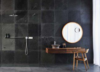 salle de bains aux murs carrelés de dalles noires avec un meuble en bois
