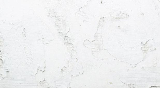 Gros plan sur les dégats des condensation et infiltration d'eau sur un mur