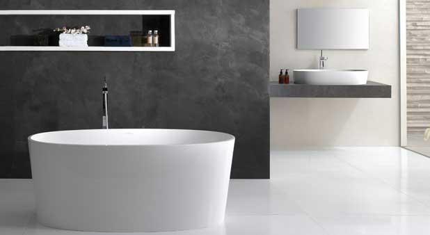 une baignoire ilot blanche devant un mur noir
