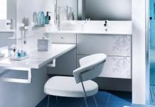 Une coiffeuse dans une salle de bains blanche qui prolonge le meuble-vasque