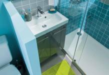 Salle de bain bleu avec WC, séparé du lavabo par un muret.