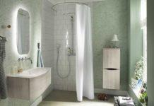 Dans une salle de bain vert céladon, une douche fermé par un rideau posé sur une tringle en arc de cercle