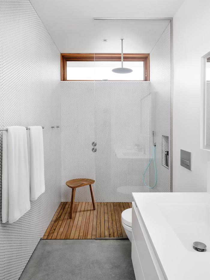 une salle de bains blanche avec du bois au sol