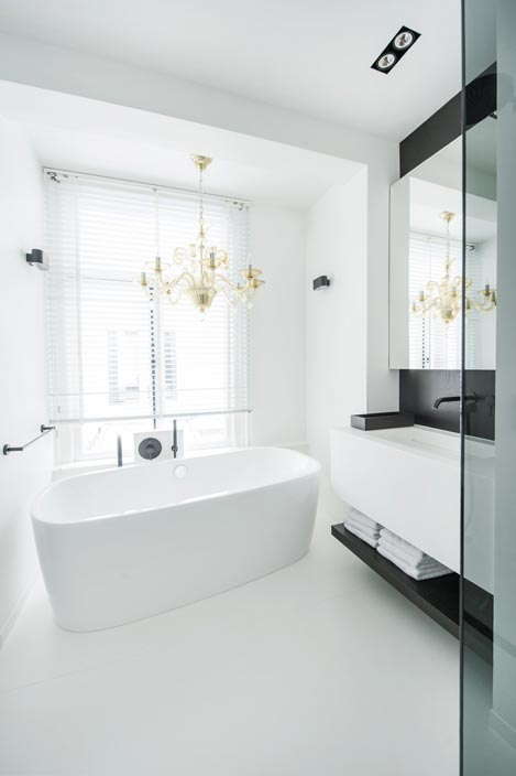 Dans une salle de bains blanche et noire, photo de la baignoire surmontée par un lustre