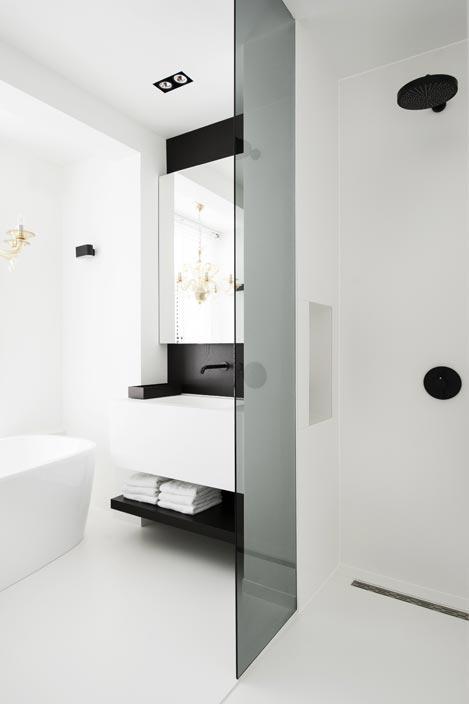 Le meuble-vasque blanc et sa robinetterie noire, dans une salle de bains blanche et noire