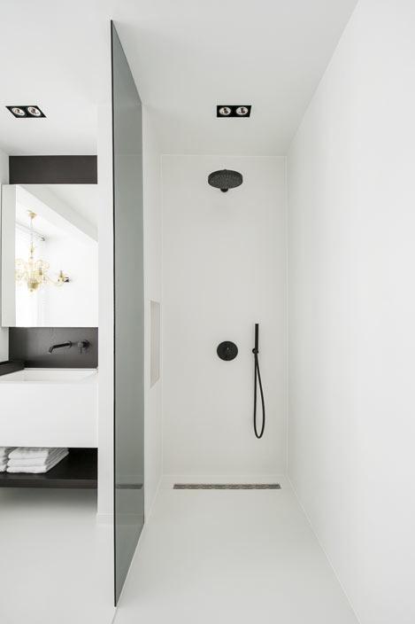 Dans une salle de bains blanche et noire, vue sur la douche