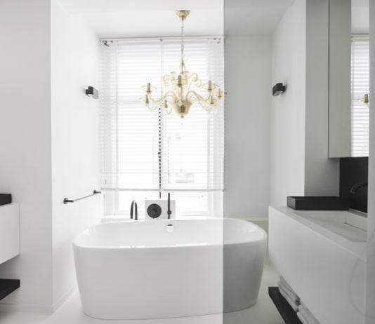 Vue sur la baignoire ilot d'une salle de bains blanche et noire