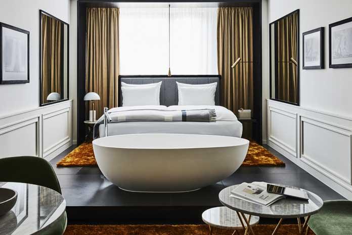 Baignoire îlot installée dans une chambre, en bout de lit