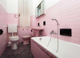 une salle de bains rose et démodée