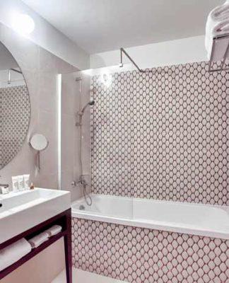 Salle de bain avec baignoire encastrée dans un décor carrelée aux motifs bicolores
