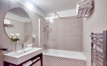 Salle de bains avec baignoire encastrée dans un décor carrelée aux motifs bicolores