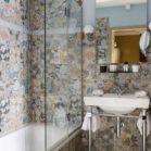 baignoire encastrée dans une salle de bains avec un patchwork de carreaux aux motifs de fleurs