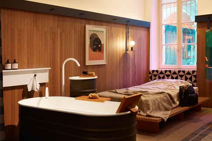 Une chambre équipée d'une baignoire et d'un lavabo totem en îlots