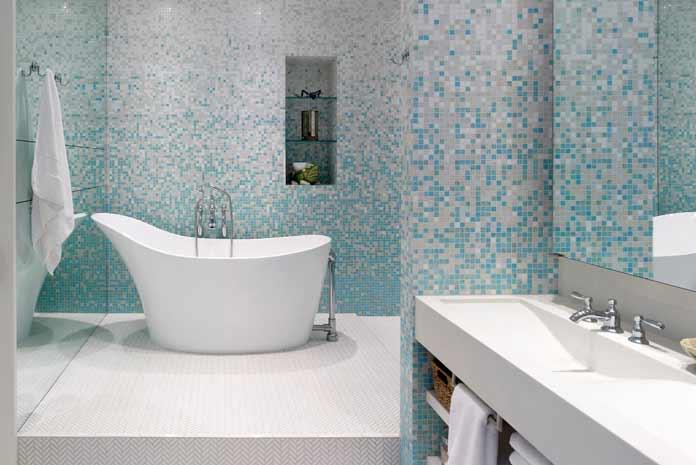 Baignoire ilot installée dans une grande douche en mosaïque