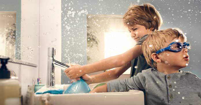 Jeunes enfants jouant avec l'eau devant un lavabo