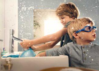 Enfants jouant avec l'eau devant le lavabo