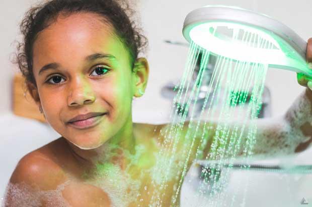 Une enfant dans la baignoire tenant une douchette à main Hydrao