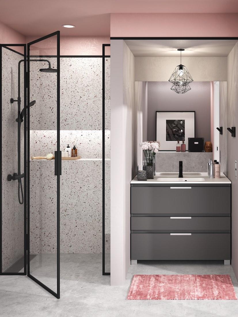 Salle de bain rose et meuble gris foncé.