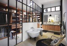 Longue verrière entre une chambre et une salle de bain