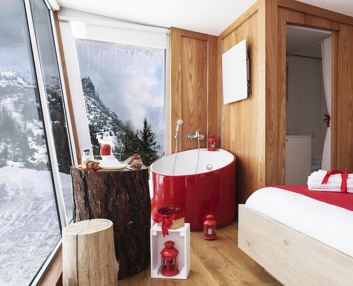 Une baignoire rouge dans une salle de bains décorée comme un chalet
