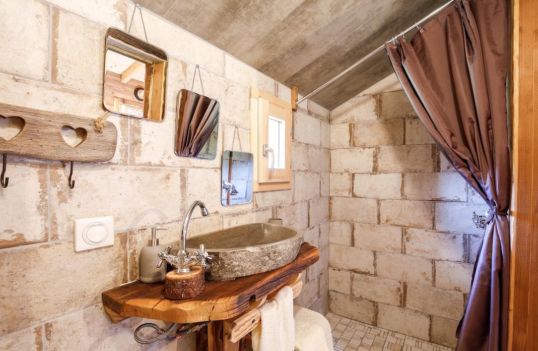 Une vasque en pierre brute sur une planche de bois