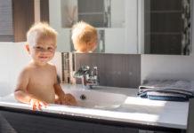 un bébé assis dans la vasque du meuble vasque