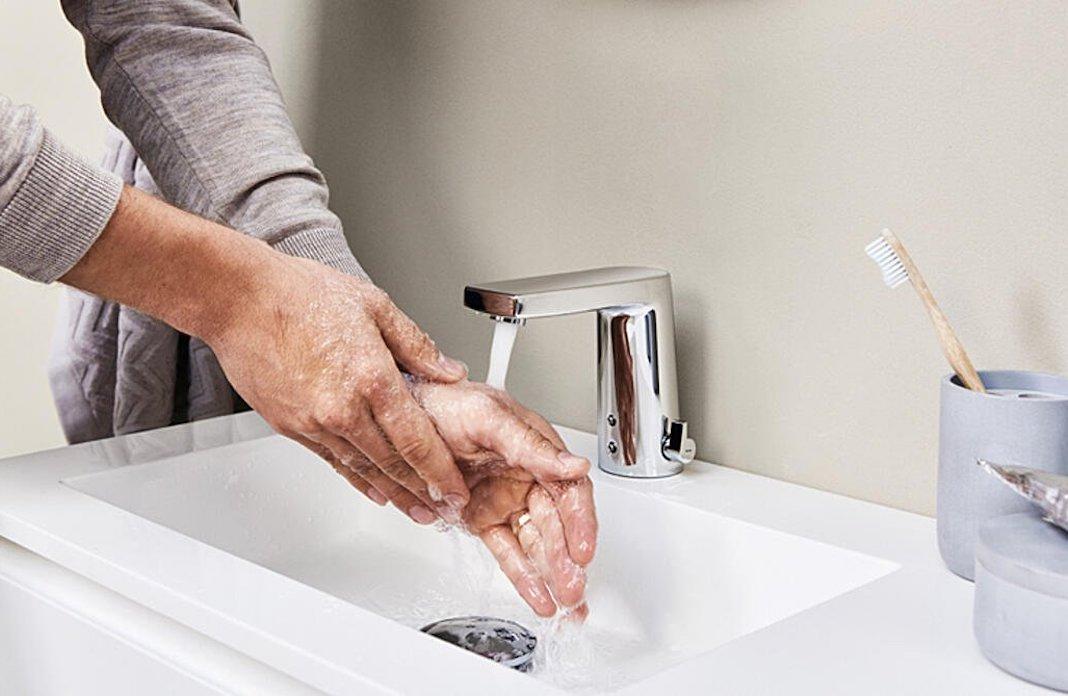 mains sous un robinet électronique