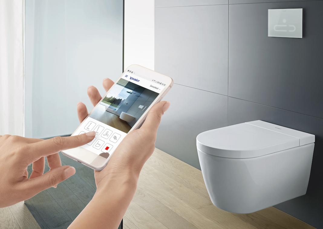 une main avec un smarphone réglant un WC lavant en arrière plan