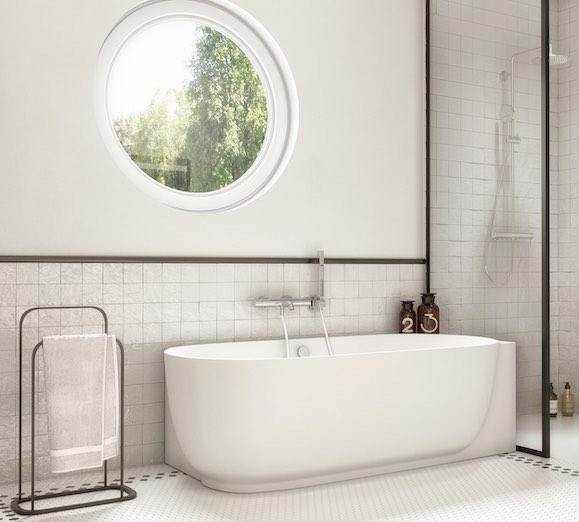 une baignoire semi ilot blanche sous une fenêtre ronde