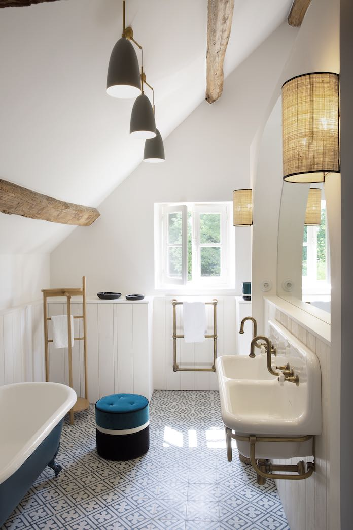 deux lavabos rétro suspendus font face à une baignoire rétro peinte en bleu