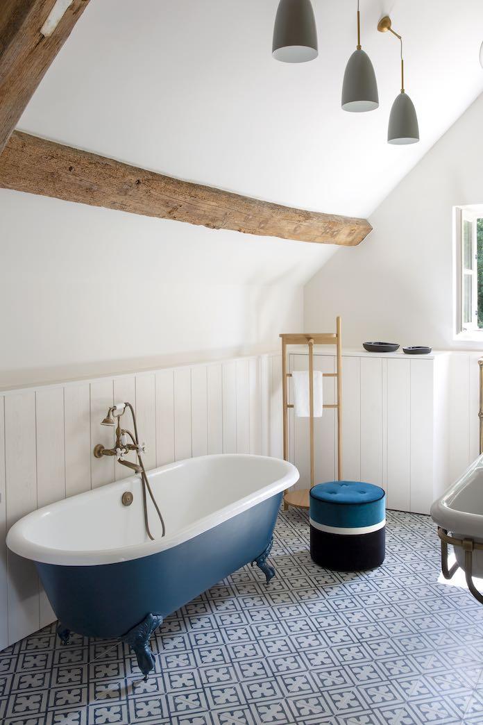 une baignoire rétro bleu devant un soubassement en bois blanc