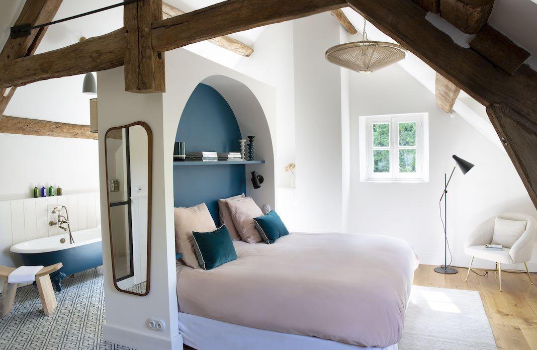 un lit adossé à une tête de lit formant la cloison de la salle de bain derrière
