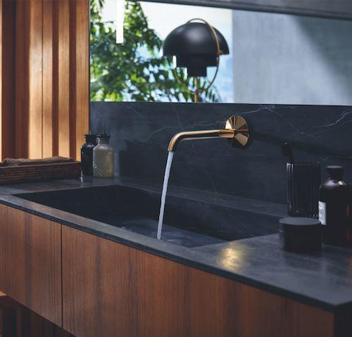 robinet mural doré sur vasque noire