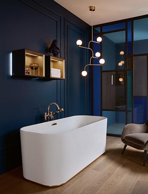 Baignoire blanche dans une salle de bains bleu foncé et dorée