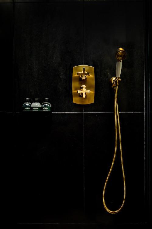 robinet doré encastré sur un mur en carrelage noir