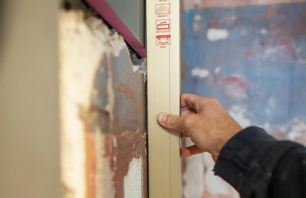 Main tenant un niveau sur un mur redressé avec des plaques Qboard