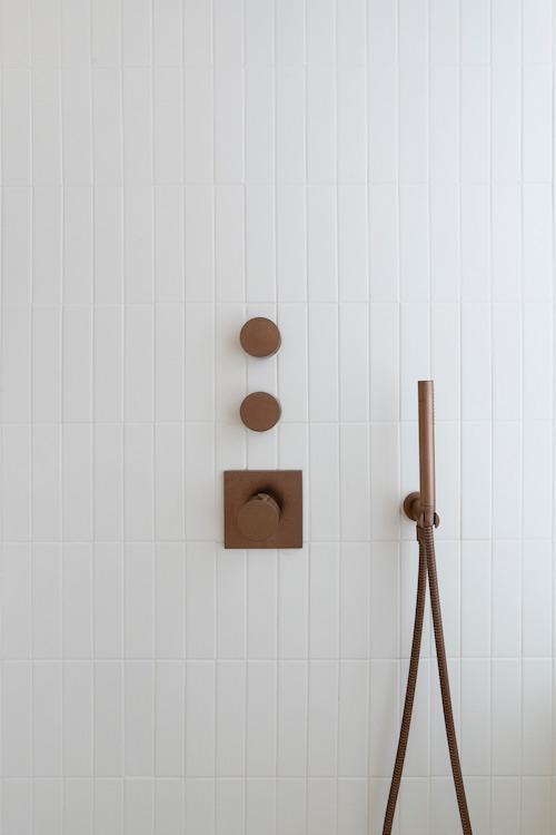 mitigeur de douche finition cuivrée encastré sur du carrelage blanc