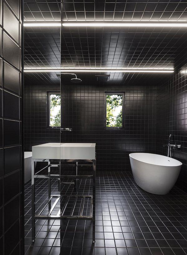 salle de bains toute carrelée avec des carreaux noirs
