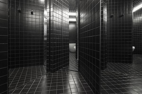 salle de bains entièrement carrelée avec des carreaux noirs