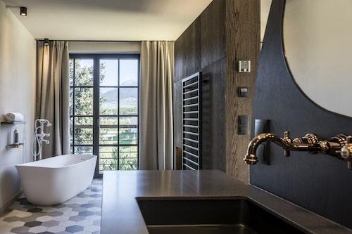 Un plan vasque et un radiateur noirs devant une baignoire ilot blanche