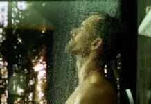 Homme sous une douche de tête Hansgrohe