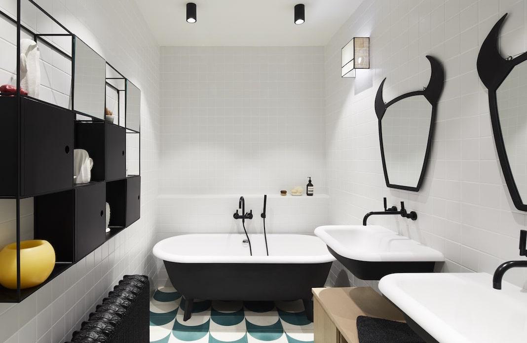salle de bain design avec une baignoire et des lavabos noirs dehors et blancs dedans