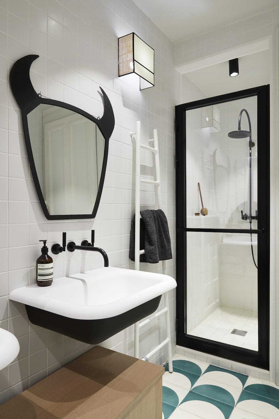 salle de bains design aux murs blancs avec un lavabo et une douche ceinturés de noir