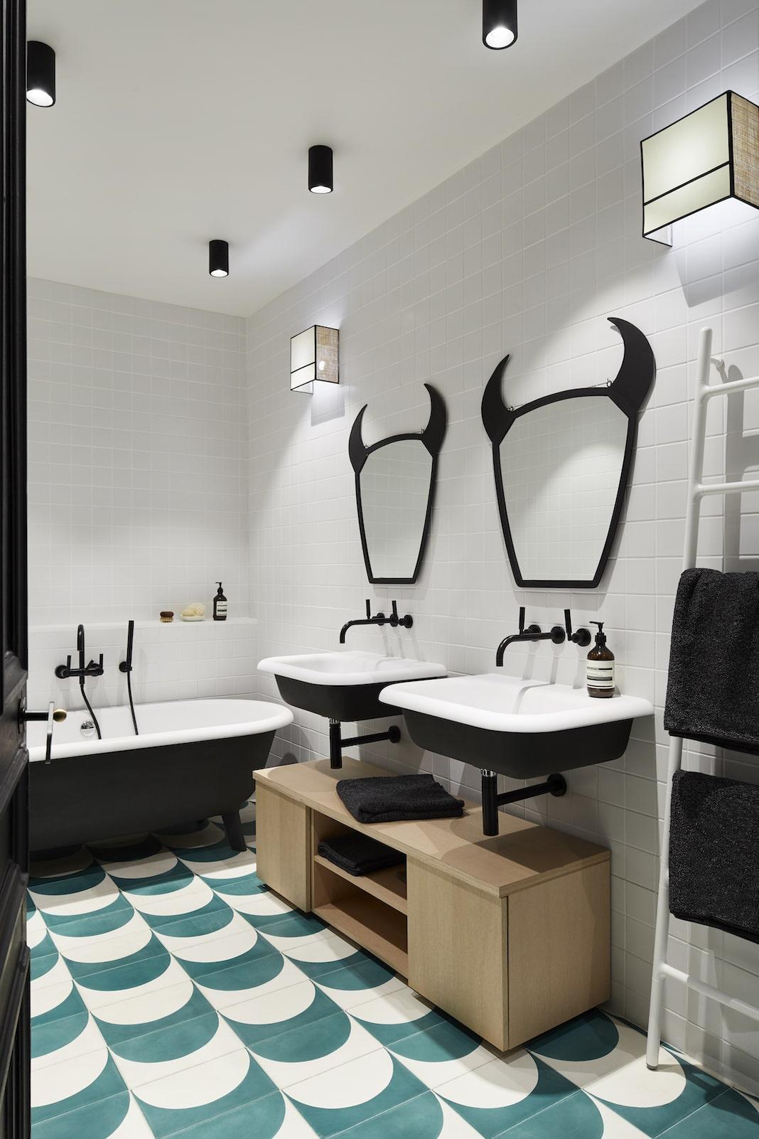 salle de bain design noire et blanche avec des miroirs cornus au dessus des lavabos
