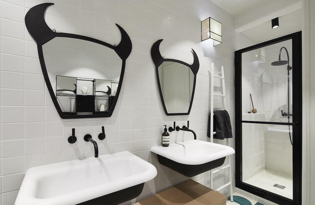 deux lavabos blancs et noirs avec des miroirs cornus au desssu