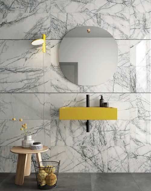 Un lavabo suspendu jaune posé sur un mur en marbre blanc
